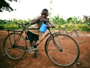 Photo courtesy of Gloria Bernard. A boy leans on his adult-sized bicycle.